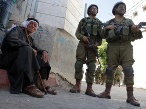 An elderly Palestinian man sits near Israeli soldiers taing part in a search operation for three Israeli teenagers believed kidnapped by Palestinian militants. Israel is using the search to root out remaining Hamas infrastructure in the West Bank.